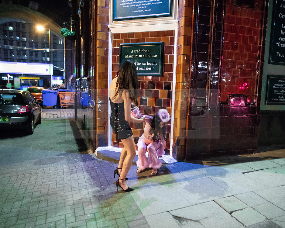 © Licensed to London News Pictures . 27/10/2018. Manchester, UK. A woman helps another up off the ground outside a pub on Charles Street in Manchester City Centre . Revellers on a night out , many in fancy dress , on the weekend before Halloween . Photo credit: Joel Goodman/LNP