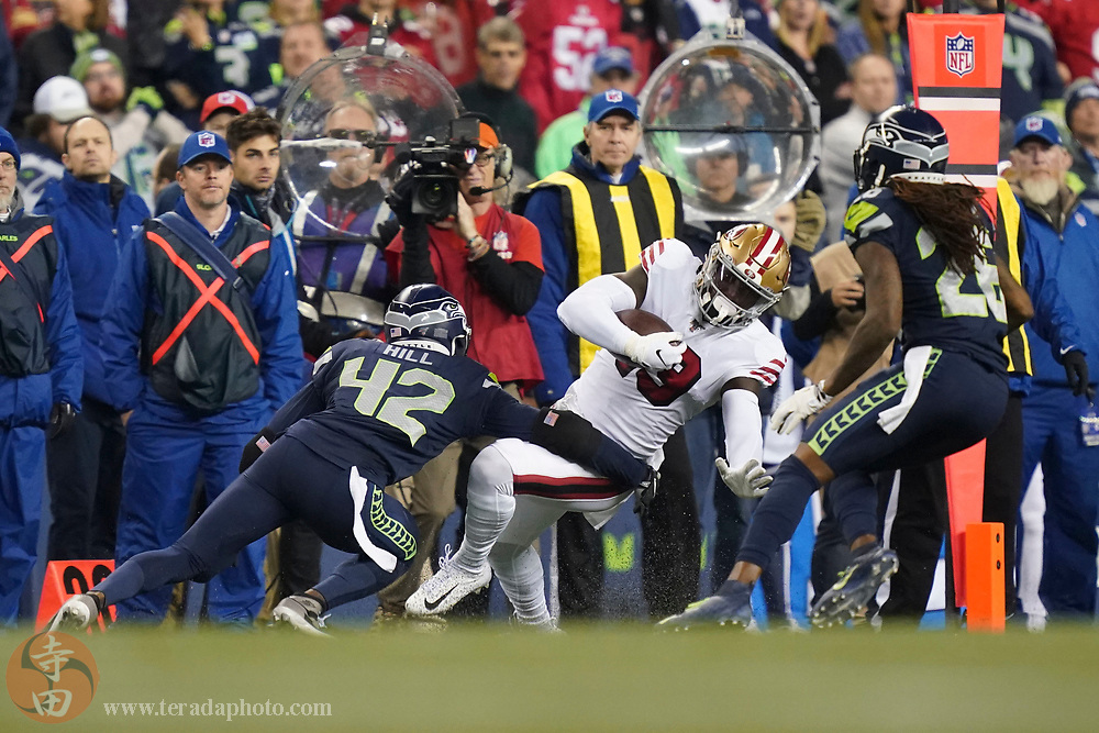 December 29, 2019; Seattle, Washington, USA; San Francisco 49ers wide receiver Deebo Samuel (19) is tackled by Seattle Seahawks defensive back Lano Hill (42) during the second quarter at CenturyLink Field.