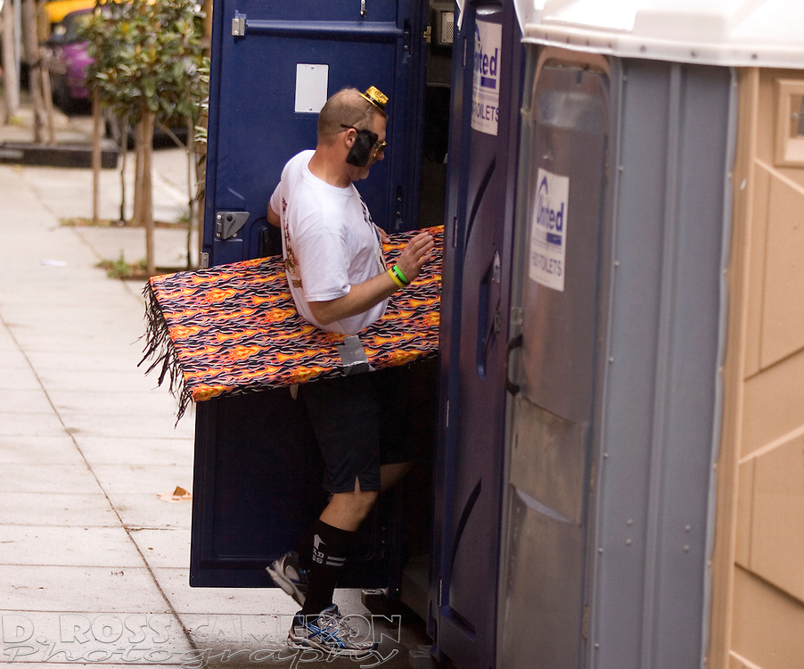Bob Lewandowski of Houston, Texas struggles to fit himself and his flying carpet into a portble toilet during the 100th running of the Bay to Breakers 12K through San Francisco, Sunday, May 15, 2011. (Photo by D. Ross Cameron)