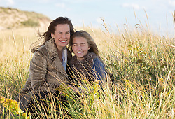 mother and daughter in tall grass at the beach