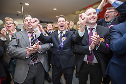 © Licensed to London News Pictures . 10/10/2014 . Heywood , UK . UKIP supporters cheer as the declaration at the Clacton count is broadcast on TV . The count at the Heywood and Middleton by-election , following the death of sitting MP Jim Dobbin . Photo credit : Joel Goodman/LNP