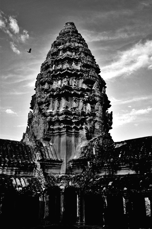This Black and White shot of Angkor Wat, the world's largest single religious monument was shot inside the courtyard of the main tower complex.<br /> <br /> Angkor Wat was built for the king Suryavarman II in the early 12th century as his state temple and capital city.<br /> <br /> It is a massive three-tiered pyramid crowned by five lotus-like towers rising 65 meters from ground level is surrounded by a moat and an exterior wall. All the walls of the temple are covered inside and out with bas-reliefs and carvings. <br /> <br /> The ruins of Angkor, a UNESCO World Heritage Site with temples numbering over 1000, are hidden amongst forests and farmland to the north of the Tonle Sap Lake outside the modern city of Siem Reap, Cambodia. <br />  <br /> It is one of the most awe-inspiring locations I have ever been. From the sunrise to the sunset, there isn't a time of day that is not simply a spectacular time to explore this breathtaking location.