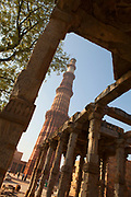 Low angle view of the Qutab Minar as seen through another one of the historical buildings in the Qutab Complex