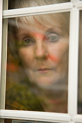 Portrait of an older woman looking out of the window,