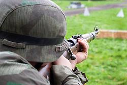 A Re-enactor portrayiing a German Panzer Grenadier wearing splinter pattern camouflage aims Kar K98 K, bolt action rifle during a battle battle re-enactment in on Pickering Showground<br /> <br /> 17/18 October 2015<br />  Image © Paul David Drabble <br />  www.pauldaviddrabble.co.uk