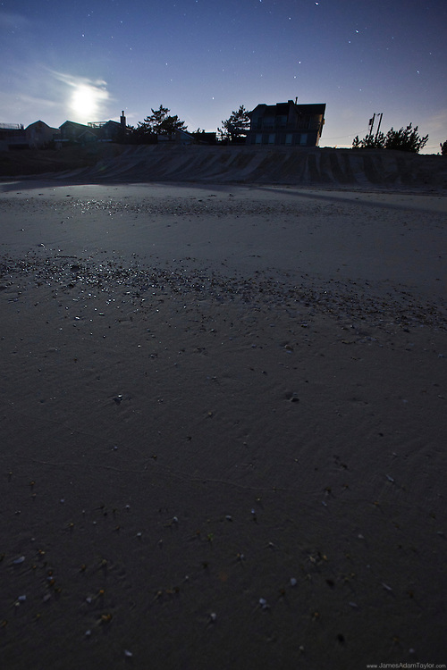 Pebbles reflect moonlight, in the distance the unnatural shape of the dunes is obvious.