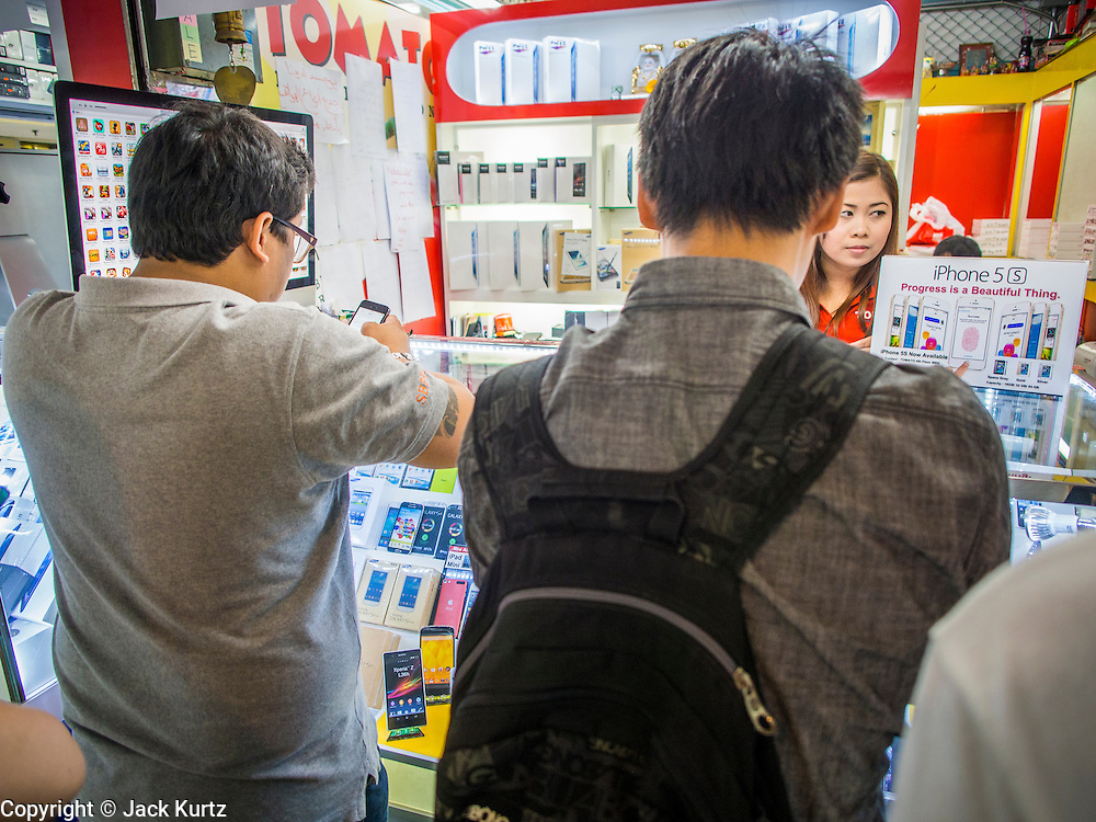 21 SEPTEMBER 2013 - BANGKOK, THAILAND: A woman sells iPhone 5s models in an electronics shop in Bangkok. Customers around the world lined up Friday to pick up Apple's new flagship iPhone 5s and its lower cost, more colorful brother, the iPhone 5c. The phones went on sale in the US and select countries beyond the US on Friday. The iPhone 5s and iPhone 5c will not be officially released in Thailand until late 2013 but the phones are available through the unofficial grey market in MBK, a huge shopping complex in Bangkok with dozens of small electronics shops. Early purchasers in Thailand pay a premium for the new iPhones, the top of the line iPhone 5s with 64 gigabytes of memory is about 38,500Baht, more than $1,200 (US).      PHOTO BY JACK KURTZ