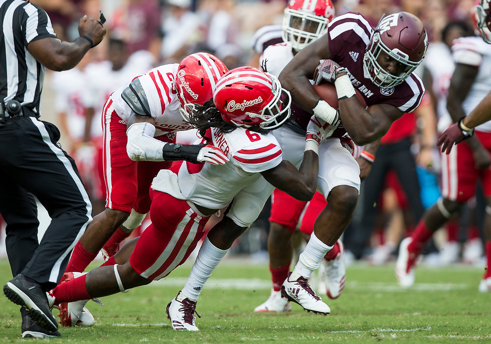 Texas A&M running back Jacob Kibodi (23) picks up yards as Louisiana-Lafayette defensive back Corey Turner (6) brings him down during the third quarter of an NCAA college football game Saturday, Sept. 16, 2017, in College Station, Texas. (AP Photo/Sam Craft)