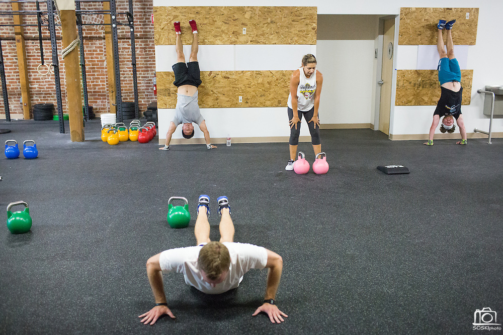 Athletes perform a circuit of pushups, squat clean and presses, and handstands during a CrossFit program at ThirdSpace Fitness in San Jose, California, on July 6, 2015. (Stan Olszewski/SOSKIphoto for Content Magazine)
