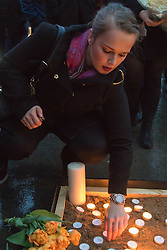 Trafalgar Square, London, March 24th 2016. A woman places a candle as people gather in London's Trafalgar Square to light candles and lay flowers in memory of those who lost their lives in the Brussels terror attacks on March 22nd in which 31 people were killed and dozens injured.