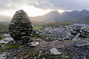 A cairn is surrounded by tons of wasted slate above the town of Blaenau Ffestiniog, on 2nd October 2021, in Blaenau Ffestiniog, Gwynedd, Wales. The derelict slate mines around Blaenau Ffestiniog in north Wales were awarded UNESCO World Heritage status in 2021. The industry's heyday was the 1890s when the Welsh slate industry employed approximately 17,000 workers, producing almost 500,000 tonnes of slate a year, around a third of all roofing slate used in the world in the late 19th century. Only 10% of slate was ever of good enough quality and the surrounding mountains now have slate waste and the ruined remains of machinery, workshops and shelters have changed the landscape for square miles.