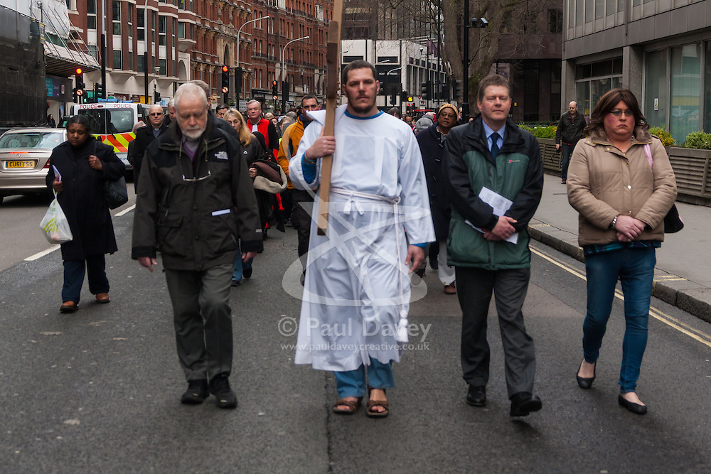 Hundreds of Christians in London take part in the interdenominational Methodist, Anglican and Catholic March of Witness in Westminster. PICTURED: A member of the homeless charity The Passage carries the cross from Westminster Cathedral towards Westminster Abbey.