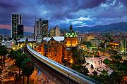 The elevated Medellin Metro is in motion as it rushes into the Parque Berrio Station in front of the illuminated Palace of Culture in Plaza Botero in Medellin, Colombia.