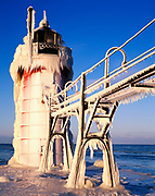Morning light illuminating ice-coverd catwalk and South Haven Pier Lighthouse, Black River, Lake Michigan, South Haven, Michigan.