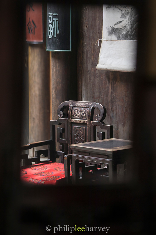 Ornate wooden chair inside of a traditional interior, Hongcun village, Anhui Province, China
