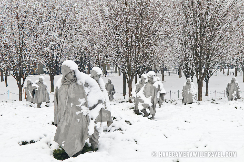"The Korean War Memorial on the National Mall after heavy snowfall. The Korean War Veterans Memorial, unveiled in 1992, sits on the northwestern end of the National Mall, not far from the Lincoln Memorial. It consists of several elements designed by different people and groups. It has a triangular footprint with the main elements being ""The Column"" consisting of 19 stainless steel solders, each over 7 feet tall, and a reflective granite wall etched with the faces of thousands of Americans who lost their lives in the war. At one end of the triangle, behind the soldiers, is a grove of trees. At the other is a large American flag and a small Pool of Remembrance. Among the designers were Frank Gaylord (the soldiers) and Louis Nelson (the reflecting granite wall)."