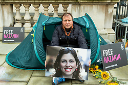 © Licensed to London News Pictures. 26/10/2021. LONDON, UK.  Richard Ratcliffe, husband of detained British-Iranian aid worker Nazanin Zaghari-Ratcliffe, on day 3 of his hunger strike outside the Foreign and Commonwealth Office demanding that the UK government tries to do more to secure her release.  Mrs Zaghari-Ratcliffe has been held in Iran since 2016 and has not seen her daughter for two years and faces a return to prison.  Photo credit: Stephen Chung/LNP