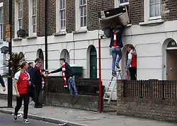 Arsenal fans help a nearby resident to get a sofa in through him Window before the Premier League match at the Emirates Stadium, London.