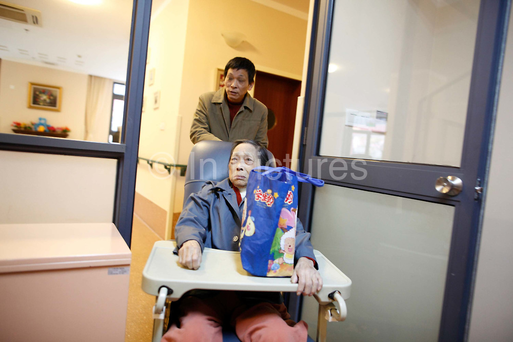 Miao Yuqiang pushes his mother, Qiu Jinzhen, who suffers from dementia, at the Shanghai 3rd Welfare House in Shanghai, China on 28 November 2010.   Dementia and Alzheimer's is fast establishing themselves as a major health risk for China's booming elderly population, placing strain on families and society a like, especially in major cities such as Shanghai, where the traditional system of large family and caring for the old by family members give way to small family units and retirement homes.