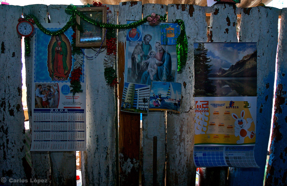 A wall with some christmas decoration, a poster of Guadalupe virgin and another of the sacred family in one popular bar in Mazatlan