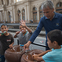 Illegal migrant children wash their teeth at a public water tap as they wait to board train at the main railway station Keleti in Budapest, Hungary on September 03, 2015. ATTILA VOLGYI