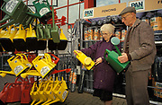 An elderly couple choose between green or yellow watering cans from the choices on offer at a B&Q DIY superstore, on 13th April 1993, in Macclesfield, England.