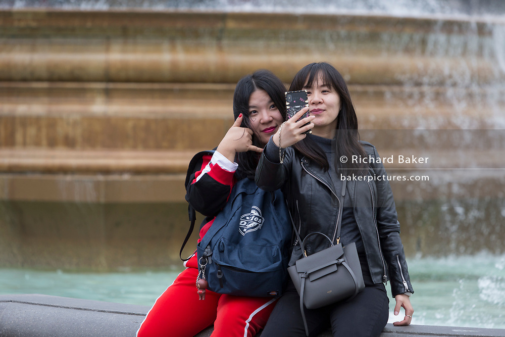 """With a background of fountains, two Asian friends take a selfie portrait with a mobile phone on which is the words """"Love You"""", in Trafalgar Square, on 20th May 2019, in London, England."""