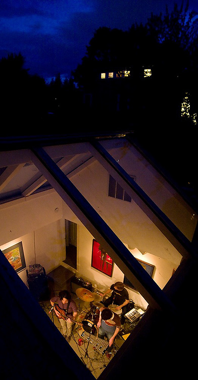 Rock band Song Sparrow Research performs at the Dearborn House in Seattle, Washington, as seen from the roof at night through a large skylight.
