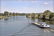 Nederland, Gennep, 29-5-2020  Een binnenvaartschip vaart over de Maas in noord limburg . Deze rivier wordt vanf Maastricht via 7 sluizen stuwen op een peil van 3 meter gehouden en heeft daardoor geen natuurlijk laagwater . Ook nu is het peil normaal.   Bij onvoldoende aanvoer van water vanuit Belgie wordt er minder geschut om water te sparen en moeten schepen soms lang wachten om de sluis door te kunnen . De grensmaas bij Maastricht is niet bevaarbaar en dus voor de scheepvaart niet van belang. Die gaan dat stuk via het Julianakanaal. De Oude maas in Zuid Holland is een getijdenrivier wat betekent dat de waterhoogte beinvloed wordt door eb en vloed.  Staatsbosbeheer en rijkswaterstaat leggen natuurgebieden aan in de uiterwaarden van de grote rivieren . Natuurontwikkeling in de uiterwaarden en rivierverruimende projecten voor een betere afvoer van het water bij hoogwater . Hier is bijvoorbeeld het natuurgebied maasheggen, een oud cultuurlandschap waarbij heggen percelen afbakenen .Foto: Flip Franssen