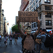 An Occupy protesters holds his placard during the march down Broadway, New York, on their way to Wall street during the Occupy May Day 2012 action day.  New York, USA. 1st May 2012. Photo Tim Clayton