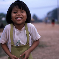 Asia, Laos, Vientiane, Portrait of smiling young girl at dusk in Muang Chanthabuli district of city