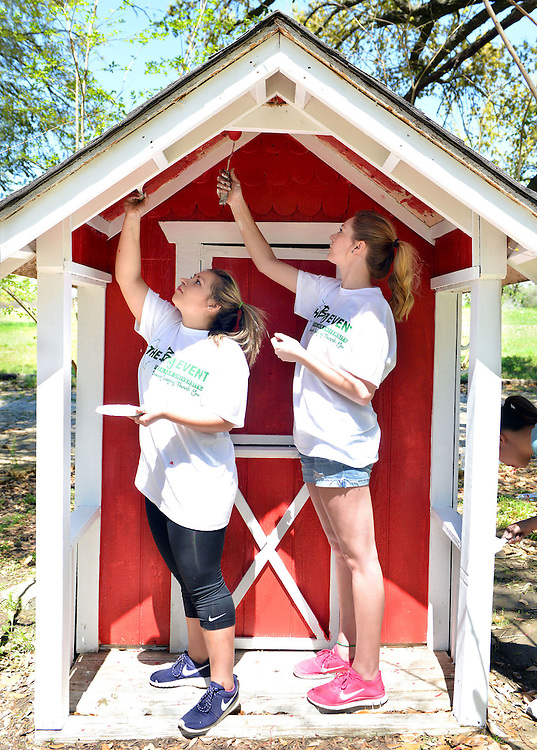 Katie Kunz, left, and Kameron Schnautz roll out red paint while repainting a small storage shed at a home on Leonard Road on Saturday as part of The Big Event.  The annual event brought out over 21,000 students to complete 2,500 jobs all over the Bryan-College Station area.