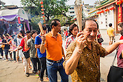 """09 FEBRUARY 2013 - BANGKOK, THAILAND:  People stand in line to get into Wat Mangkon Kamalawat in Chinatown in Bangkok. Wat Mangkon Kamalawat is the largest Chinese temple in Bangkok and crowded on Chinese holiday with people offering prayers and making merit. Bangkok has a large Chinese emigrant population, most of whom settled in Thailand in the 18th and 19th centuries. Chinese, or Lunar, New Year is celebrated with fireworks and parades in Chinese communities throughout Thailand. The coming year will be the """"Year of the Snake"""" in the Chinese zodiac.   PHOTO BY JACK KURTZ"""