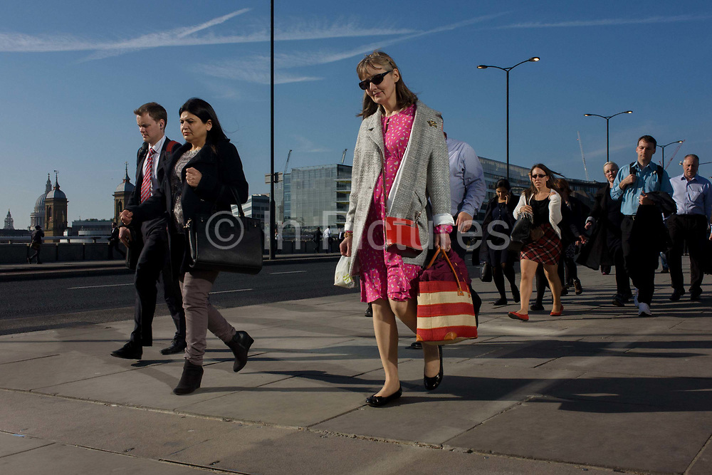Londoners cross southbound over London Bridge during  the evening rush hour. A woman in pink is lost in thought behind dark sungalsses. Commuters stride alongside others walking out of the City of London. There has been a crossing over the Thames here since the Romans first forded the river in the early 1st Century with subsequent medieval and Victorian stone bridges becoming an important thoroughfare from the City on the north bank, to Southwark on the south where transport hubs such as the mainline station gets commuters to the suburbs and satellite towns.