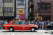 A taxi passes a mikoshi as is carried through the street during the Sanja matsuri, Asakusa, Tokyo, Japan. Sunday May 21st 2017. The Sanja matsuri (Three shrines festival) is one of the biggest Shinto festivals in Japan. It takes place for 3 days around the third weekend of May and features over 100 large and small mikoshi, or portable shrines, which are paraded around the streets of the historic Asakusa district in Tokyo. to bring blessings and good luck on the inhabitants. The events attracts up to 2 million visitors each year.