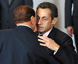 """Nicolas Sarkozy, France's president, right, whispers in the ear of Silvio Berlusconi, Italy's prime minister, during the """"Family Photo"""" session at the European Summit, in Brussels, Belgium, Wednesday, Oct. 15, 2008.   (Photo © Jock Fistick)"""