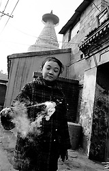 Girl holding firework at Chinese New Year in a Beijing hutong