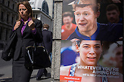 Businesswoman walks past a poster ad for City of London Fitness First gyms.