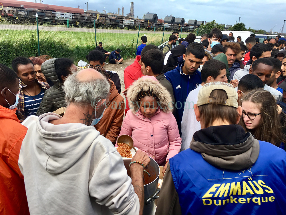30July2021. Calais, France.<br /> Long lines gather for lunch as British founded charity Care4Calais along with other charities offer food, assistance, phone charging, haircuts, clothing, tents and more to migrant refugees in Dunkerque. A new 'Jungle' appears to be springing up from the trees and woods on the outskirts of Dunkerque where conditions are not as hostile or inhospitable as they are currently in Calais 30km to the south.<br /> Photo©; Charlie Varley/varleypix.com