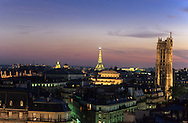 France. Paris. Elevated view on Paris cityscape and the Eiffel tower. Saint jacques tower. the eiffel tower and panoramic view  view from the dome of the bazar de l'hotel de ville       The Eiffel Tower and Tour St.-Jacques stand illuminated against a colorful sky at twilight in Paris. Tour St.-Jacques was once the tower of the Boucherie church.