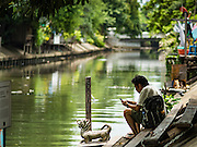 27 AUGUST 2016 - BANGKOK, THAILAND:  A man checks his smart phone on the bank of a canal that runs past the Pom Mahakan slum in central Bangkok. The Pom Mahakan community is known for fireworks, fighting cocks and bird cages. Mahakan Fort was built in 1783 during the reign of Siamese King Rama I. It was one of 14 fortresses designed to protect Bangkok from foreign invaders. Only two of the forts are still standing, the others have been torn down. A community developed in the fort when people started building houses and moving into it during the reign of King Rama V (1868-1910). The land was expropriated by Bangkok city government in 1992, but the people living in the fort refused to move. In 2004 courts ruled against the residents and said the city could evict them. The city vowed to start the evictions on Sept 3, 2016, but this week Thai Prime Minister Gen. Prayuth Chan-O-Cha, sided with the residents of the fort and said they should be allowed to stay. Residents are hopeful that the city will accede to the wishes of the Prime Minister and let them stay.      PHOTO BY JACK KURTZ