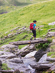 Woman hiker crossing wooden bridge, Gavarnie, France