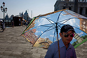 Chinese tourist with umbrella in Piazza San Marco, Venice, Italy. The wide expanse of Piazza San Marco is in the heart of Venice and where, for most daylight hours, the pavement is crowded with humanity as the influx of tourists who, in their own way, flood the narrow streets with sun-shading umbrellas and the smaller canals with gondolas. Venice attracts 22-million visitors each year (for a city of only about 60,000 residents) while the cultural protection organisation, Italian Nostra, warns that Venice can only accommodate about 33,000 visitors per day but currently at least 60,000 daily.