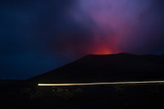 The glow of the lava lake and ongoing strombolian eruptions can be seen lighting up the sky above Mt Yasuur as vehicles drive into the volcanic area on the East side of Tanna Island.
