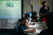 """BIRMINGHAM, AL – MARCH 7, 2017: Third grader Courtney Crosby (center) at Glen Iris Elementary practices the upstroke during a cursive writing class with Afsaneh Beauvais. Beauvais, an elementary school teacher of three years, believes cursive writing is valuable even in the digital world. """"It's relevant to real life,"""" Beauvais said. """"If nothing else, everybody has to sign their name."""" <br /> <br /> With the adoption of Common Core standards in 2010, school districts have begun to weigh the value of cursive writing compared to modern communication methods favoring laptops, tablets and cell phones. The discipline, once considered an academic rite of passage for young students, is now at risk of being replaced as school districts nationwide weigh the value of cursive writing.<br /> CREDIT: Bob Miller for The Wall Street Journal<br /> CURSIVE"""