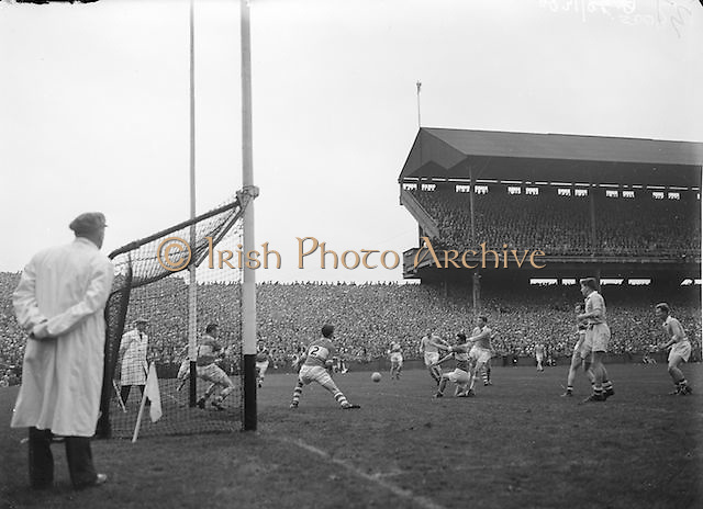 Umpire watches as Dublin makes a shoot at the goal but it goes wide during the All Ireland Senior Gaelic Football final Dublin vs Derry in Croke Park on 28th September 1958. Dublin 2-12 Derry 1-9.
