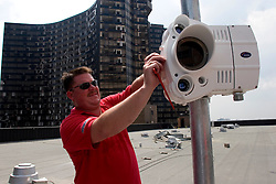 10 Sept 2005. New Orleans, Louisiana. Hurricane Katrina aftermath. <br /> Gerald Bartlett installs infra red free space optic radio links atop the lower roof of the devastated Hyatt hotel as Unisys begins the task of reconnecting the city to its Government.<br /> Photo; ©Charlie Varley/varleypix.com