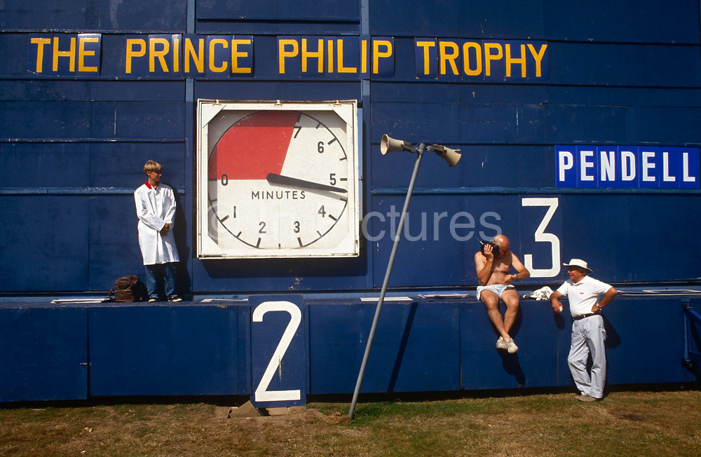 "Match officials at a Cartier polo tournament in Windsor Great Park, London. As time ticks on during the chukka, a scorer in a long white coat stands watching another as he checks his watch and listens to a transistor radio. We see that one team of the Prince Philip Trophy is Pendell Polo stables from Reading, England who have scored 3 points. Polo - from pulu in Hindi - referring to the wooden ball which was used, was adopted by the sport in its slow spread to the west. The first polo club was established in the town of Silchar in Assam, India, in 1834. It is also  called ""The Sport of Kings"" and is a team sport played on horseback in which the objective is to score goals against an opposing team."