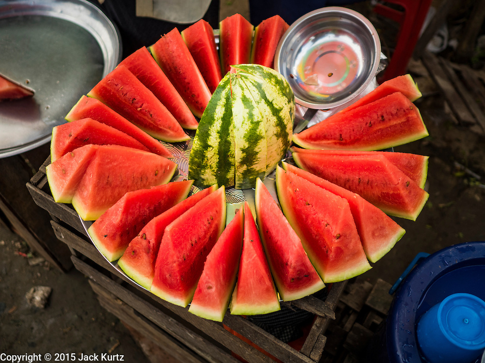"""25 OCTOBER 2015 - INSEIN, MYANMAR:  Watermelon for sale by the slice at Danyin Market (also known as Da Nyin) in Insein, Myanmar, about 90 minutes from Yangon. Vendors in the market sell just about everything people in the area need, but mostly it's a """"wet market"""" with fruits, vegetables and meats. Most people in Myanmar still do not have refrigerators in their homes, so people go to market almost every day.    PHOTO BY JACK KURTZ"""
