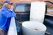 22 OCTOBER 2007 -- MONUMENT VALLEY, UT: DALE HOLLIDAY waits for his grandson to fill a 50 gallon barrel with potable water at the well at Goulding's Trading Post in Monument Valley. More than 30 percent of the homes on the Navajo Nation, about the size of West Virginia and the largest Indian reservation in the US, don't have indoor plumbing or a regular supply of domestic water. Many of these homes have to either buy water from commercial vendors or haul water from public wells. A Federal study showed that the total cost of hauling water was about $113 per 1,000 gallons. A Phoenix household, in comparison, pays just $5 a month for up to 7,400 gallons of water. The lack of water on the reservation means the Navajo are among the most miserly users of water in the United States. Families that have to buy or haul water use only about 15 gallons of water per day per person. In Phoenix, by comparison, the average water use is about 170 gallons per day.  Photo by Jack Kurtz